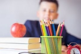 back to school marketing ideas - stacks of books with apple on top, eyeglasses, alarm clock and bunch of pencils